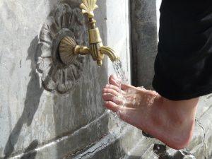Umývanie nôh pod tečúcou vodou